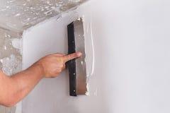 Βελτίωση σπιτιών ο εργαζόμενος βάζει το στρώμα λήξης του στόκου στον τοίχο στοκ εικόνες