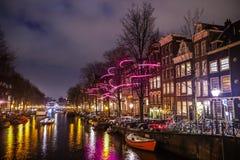 Βιασύνη βαρκών κρουαζιέρας στα κανάλια νύχτας Ελαφριές εγκαταστάσεις στα κανάλια νύχτας του Άμστερνταμ μέσα στο ελαφρύ φεστιβάλ στοκ εικόνες