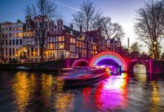 Βιασύνη βαρκών κρουαζιέρας στα κανάλια νύχτας Ελαφριές εγκαταστάσεις στα κανάλια νύχτας του Άμστερνταμ μέσα στο ελαφρύ φεστιβάλ στοκ εικόνα με δικαίωμα ελεύθερης χρήσης