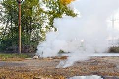 Βιασύνη της υπόγειας σωλήνωσης με το ζεστό νερό Ο ατμός αυξάνεται από τους υπονόμους στοκ φωτογραφία