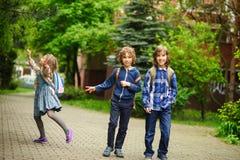 Βιασύνη τριών μικρή φίλων στα μαθήματα στο σχολείο στοκ εικόνες