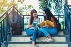 Βιβλία ανάγνωσης και παράδοσης ιδιαίτερων μαθημάτων δύο ασιατικά κοριτσιών ομορφιάς για την τελική εξέταση από κοινού Σπουδαστής  στοκ εικόνα