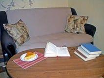Βιβλία ανάγνωσης με μια νόστιμη πίτα στον καναπέ στοκ φωτογραφίες