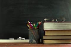 Βιβλία δασκάλων γυαλιών και μια στάση με τα μολύβια στον πίνακα, στο υπόβαθρο ενός πίνακα με την κιμωλία Η έννοια του teac στοκ φωτογραφία με δικαίωμα ελεύθερης χρήσης