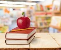 Βιβλία, μήλο και μολύβι στον ξύλινο πίνακα Στοκ φωτογραφία με δικαίωμα ελεύθερης χρήσης