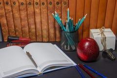 Βιβλία με ένα μήλο και μολύβια στον πίνακα βιβλία και ένα μήλο Βιβλία με τα χαρτικά στον πίνακα Στοκ Φωτογραφίες
