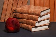 Βιβλία με ένα μήλο και μολύβια στον πίνακα βιβλία και ένα μήλο Βιβλία με τα χαρτικά στον πίνακα Στοκ φωτογραφία με δικαίωμα ελεύθερης χρήσης