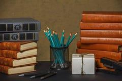 Βιβλία με ένα μήλο και μολύβια στον πίνακα βιβλία και ένα μήλο Βιβλία με τα χαρτικά στον πίνακα Στοκ Φωτογραφία