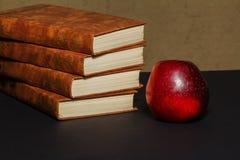 Βιβλία με ένα μήλο και μολύβια στον πίνακα βιβλία και ένα μήλο Βιβλία με τα χαρτικά στον πίνακα Στοκ Εικόνες