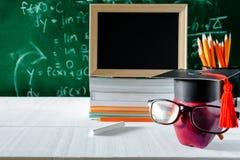 Βιβλία συμβόλων και μολυβιών γνώσης της Apple στο γραφείο Στοκ Φωτογραφίες