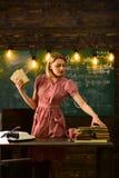 Βιβλία: Τρόφιμα για τον εγκέφαλο Όμορφο κορίτσι που διαβάζει ένα βιβλίο στο φλυτζάνι με ένα ζεστό ποτό ανάγνωση κοριτσιών βιβλίων Στοκ Εικόνα