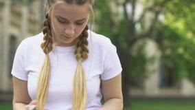 Βιβλίο ανάγνωσης έφηβη υπαίθρια, θυσμένος τις πληροφορίες, που προετοιμάζονται για το διαγωνισμό απόθεμα βίντεο