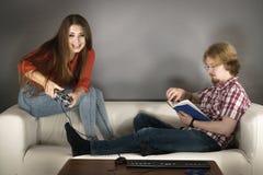 Βιβλίο ανάγνωσης ανδρών παιχνιδιών παιχνιδιού γυναικών Στοκ φωτογραφία με δικαίωμα ελεύθερης χρήσης