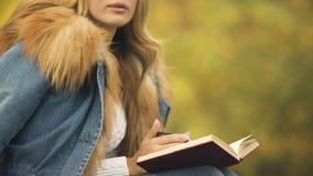 Βιβλίο ανάγνωσης γυναικών και τσάι κατανάλωσης στο κατώφλι, που απολαμβάνει τον καιρό πτώσης, ευχαρίστηση απόθεμα βίντεο