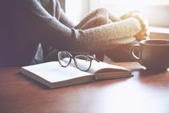 Βιβλίο ανάγνωσης γυναικών με το φλυτζάνι του τσαγιού Στοκ φωτογραφία με δικαίωμα ελεύθερης χρήσης