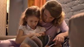 Βιβλίο ανάγνωσης μητέρων σε λίγη χαριτωμένη κόρη και συνεδρίαση μαζί στο σύγχρονο καθιστικό, οικογενειακή έννοια, στο εσωτερικό απόθεμα βίντεο
