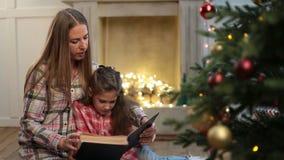 Βιβλίο ανάγνωσης μητέρων στην κόρη κοντά στο χριστουγεννιάτικο δέντρο απόθεμα βίντεο