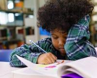 Βιβλίο ανάγνωσης μικρών παιδιών στη βιβλιοθήκη στοκ εικόνες