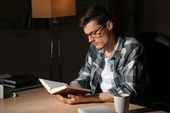 Βιβλίο ανάγνωσης νεαρών άνδρων αργά το βράδυ στοκ εικόνα με δικαίωμα ελεύθερης χρήσης