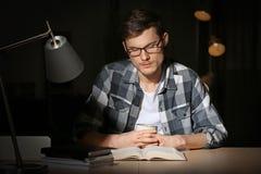 Βιβλίο ανάγνωσης νεαρών άνδρων αργά το βράδυ στοκ εικόνα