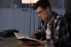 Βιβλίο ανάγνωσης νεαρών άνδρων αργά το βράδυ στοκ φωτογραφίες με δικαίωμα ελεύθερης χρήσης