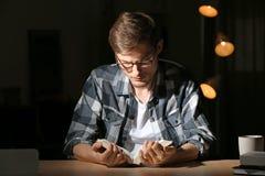 Βιβλίο ανάγνωσης νεαρών άνδρων αργά το βράδυ στοκ φωτογραφία