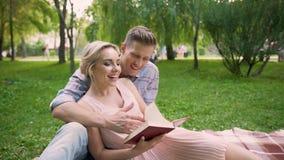 Βιβλίο ανάγνωσης τύπων στη φίλη του, ζεύγος που απολαμβάνει τον ελεύθερο χρόνο στο πάρκο από κοινού φιλμ μικρού μήκους