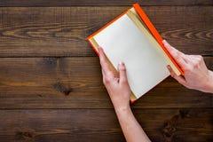 βιβλίο ανοικτό Τα χέρια κρατούν το βιβλίο βιβλίων με σκληρό εξώφυλλο ανοιγμένο στο σκοτεινό ξύλινο διάστημα αντιγράφων άποψης υπο Στοκ εικόνες με δικαίωμα ελεύθερης χρήσης