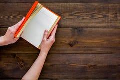 βιβλίο ανοικτό Τα χέρια κρατούν το βιβλίο βιβλίων με σκληρό εξώφυλλο ανοιγμένο στο σκοτεινό ξύλινο διάστημα αντιγράφων άποψης υπο Στοκ φωτογραφία με δικαίωμα ελεύθερης χρήσης