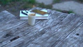 Βιβλίο, γυαλιά, καφές και κινητός σε έναν παλαιό πίνακα απόθεμα βίντεο