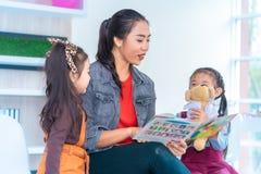 Βιβλίο ιστορίας ανάγνωσης δασκάλων στους σπουδαστές παιδικών σταθμών στοκ φωτογραφία με δικαίωμα ελεύθερης χρήσης
