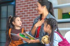 Βιβλίο ιστορίας ανάγνωσης δασκάλων στους σπουδαστές παιδικών σταθμών στοκ εικόνα