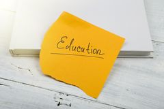 Βιβλίο και κίτρινο φύλλο με & x22 education& x22  επιγραφή σε ένα άσπρο wo Στοκ εικόνα με δικαίωμα ελεύθερης χρήσης