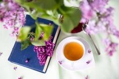 Βιβλίο και τσάι και μια μεγάλη ανθοδέσμη του ιώδους υποβάθρου άνοιξη Στοκ Εικόνα