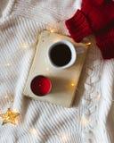 Βιβλίο, καφές, κόκκινο κερί, κόκκινα γάντια ή μάλλινα γάντια και φω'τα σε ένα άσπρο πουλόβερ στοκ φωτογραφίες