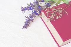 Βιβλίο του κόκκινου χρώματος με τα λουλούδια σε ένα άσπρο υπόβαθρο Στοκ εικόνες με δικαίωμα ελεύθερης χρήσης