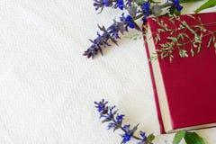 Βιβλίο του κόκκινου χρώματος στα λουλούδια σε έναν άσπρο ιστό Στοκ Εικόνα