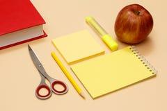 Βιβλίο, ψαλίδι, μολύβι, σημειωματάριο, επιστολόχαρτο, στυλοί πίλημα-ακρών και μήλο στο μπεζ υπόβαθρο στοκ φωτογραφίες