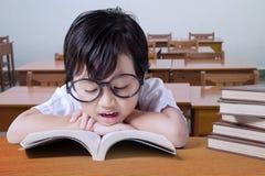 Βιβλία ανάγνωσης μικρών κοριτσιών στο γραφείο στην κατηγορία Στοκ εικόνα με δικαίωμα ελεύθερης χρήσης