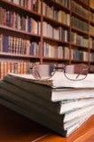 Βιβλία και γυαλιά στον πίνακα βιβλιοθηκών Στοκ Εικόνες