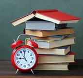 Βιβλία και ξυπνητήρι στον πίνακα πίσω σχολείο Στοκ εικόνες με δικαίωμα ελεύθερης χρήσης