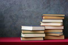 Βιβλία με τις χρωματισμένες καλύψεις στον πίνακα με ένα κόκκινο τραπεζομάντιλο Στοκ φωτογραφίες με δικαίωμα ελεύθερης χρήσης
