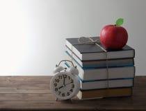 Βιβλία με το συναγερμό και την κόκκινη Apple Στοκ Εικόνες