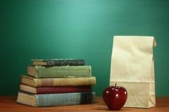 Βιβλία, Apple και μεσημεριανό γεύμα στο γραφείο δασκάλων Στοκ Φωτογραφία