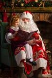 Βιβλίο ανάγνωσης Άγιου Βασίλη και μικρών κοριτσιών Στοκ φωτογραφία με δικαίωμα ελεύθερης χρήσης