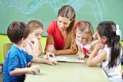 Βιβλίο ανάγνωσης δασκάλων βρεφικών σταθμών μεγαλοφώνως στοκ εικόνες