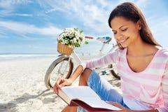 Βιβλίο ανάγνωσης γυναικών ποδηλάτων παραλιών Στοκ Φωτογραφία