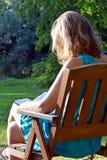 Βιβλίο ανάγνωσης γυναικών σε έναν κήπο στοκ φωτογραφία με δικαίωμα ελεύθερης χρήσης