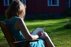 Βιβλίο ανάγνωσης γυναικών σε έναν κήπο στοκ φωτογραφίες