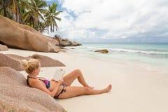 Βιβλίο ανάγνωσης γυναικών στην τέλεια παραλία Anse Patates εικόνων στο νησί Λα Digue, Σεϋχέλλες Στοκ Φωτογραφία